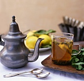 Citrus Tea in Glass Cup with Metal Tea Pot