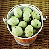 Green chocolate mini eggs in a pail