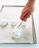 A hand spooning meringue mixture onto a baking tray