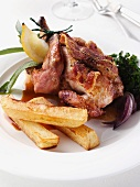 A whole roast poussin with game chips and red onions editorial food