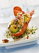A lobster shell stuffed with lobster meat, prawns, avocado, onions and sprouts