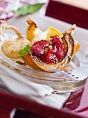 Kürbisspalte gefüllt mit Cranberrykompott, braunem Zucker und Pekannüssen