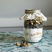 A jar containing dry ingredients for making walnut chocolate chip cookies