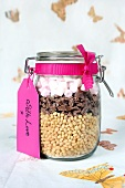 A preserving jar containing dry ingredients for making puffed rice and chocolate bars with marshmallows