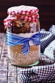 Trockene Zutaten für Walnuss-Hafer-Plätzchen mit Chocolate Chips in einem Einmachglas