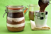 A jar containing dry ingredients for almond mocha, to one side a cup and measuring jug with coffee mixture