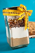 Trockene Zutaten für Kokos-Früchte-Kuchen in einem Einmachglas