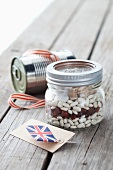 A jar containing dry ingredients for making baked beans, with a Union Jack flag and a food tin to one side