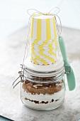 Trockene Zutaten für Bananenbrot in einem Einmachglas und Backförmchen
