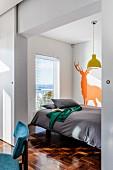 Schlafbereich mit Tiersilhouette als Wandtattoo, durch Schiebetür vom Essplatz abgegrenzt