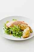 Poached salmon fillet with mustard sauce on a bed of salad