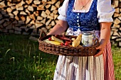 A woman wearing a dirndl and carrying a tray holding a light meal