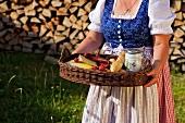 Frau im Dirndl trägt Tablett mit Brotzeit
