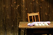 Dough balls covered with a tea towel on a wooden table outside a wooden cabin