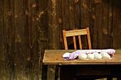 Hefeteigkugeln mit Küchentuch abgedeckt auf Holztisch vor Holzhütte