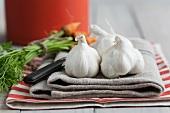 Knoblauchknollen und Babykarotten auf Leinentuch