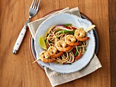 Spaghetti with vegetables and a prawn skewer