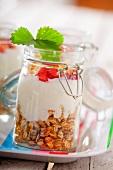 Zutaten für Müsli in einem Glas: Haferflocken, Vanillejoghurt und Erdbeeren