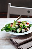Greek salad with basil, cucumber, tomato, olives and radish