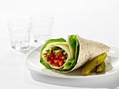 A wrap filled with vegetable batons and salad