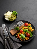 Salmon fillet with colourful vegetables on a black plate, with pesto