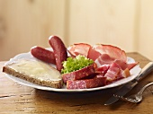 A cold meat platter with a slice of buttered bread
