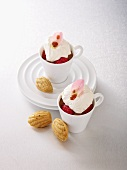 Chocolate and coffee mousse topped with raspberries and cream, with madeleines