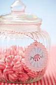 A jar of pink and white striped sweets
