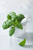 Fresh basil in a mortar with a pestle