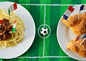 Spaghetti (Italy) and croissants (France) with football-themed decoration