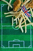 Fish and chips (England) with a paper Union Jack flag and football-themed decoration