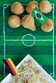 Salgadinhos (Brazil) and sauerkraut (Germany) with football-themed decoration