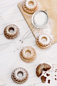 Mini Bundt cakes on grease-proof paper and on a wooden board with a sieve and icing sugar