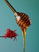 Honey flowing from a honey dipper, and saffron threads