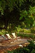 Stoffbespannte Liegestühle in der Abendsonne auf einem Holzdeck im Garten