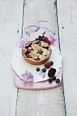 Individual berry tart with buttery crumble on a pink board