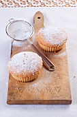 Vanilla muffins with icing sugar on a wooden board