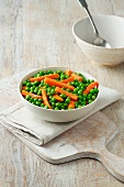 Peas and carrots in white bowl on cream cotton cloth