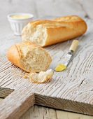White baguette with butter on white wooden board