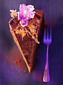 A slice of chocolate layer cake with caramel and candied flowers