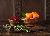 Ingredients to create Clementine and Cranberry Lamb Rack. Clementines in woven wooden bowl, cranberries in small wooden bowl and sprigs of rosemary