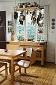 Essplatz mit Holzstühlen und Holztisch in skandinavischem Stil vor hobelbankartigem Regal an Fenster; von Decke abgehängtes Regal mit Kochgeschirr
