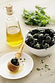 Black olives in a bowl, with parsley and olive oil