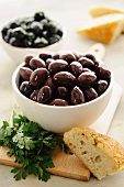 Kalamata olives in a bowl, with parsley and bread