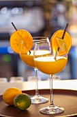 Orange and lime drink in two wine glasses