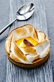 Individual lemon meringue tart and spoon on a silver-grey cloth