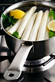 Peeled white asparagus in a saucepan with lemon and parsley