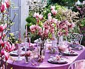 Festlich gedeckter Tisch mit rosa Magnolien und Weidenzweigen
