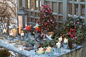 Christmas table arrangement with decorated sugar cone pines, wreath, lanterns, candles and pine cones