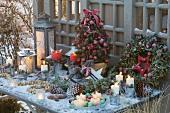 Weihnachtliches Tischarrangement mit geschmückter Zuckerhutfichte, Kranz, Laternen, Kerzen und Zapfen